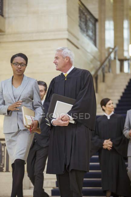 Суддя і адвокат ходьба разом через будівлю суду — стокове фото