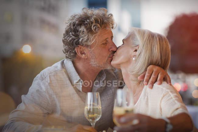Affectionate senior couple kissing drinking white wine at sidewalk cafe — Stock Photo