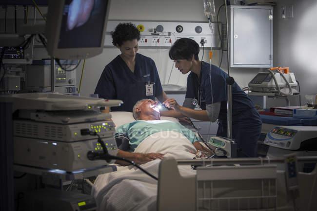 Reife Frauen Arzt und Krankenschwester Untersuchung des Patienten Kehle — Stockfoto