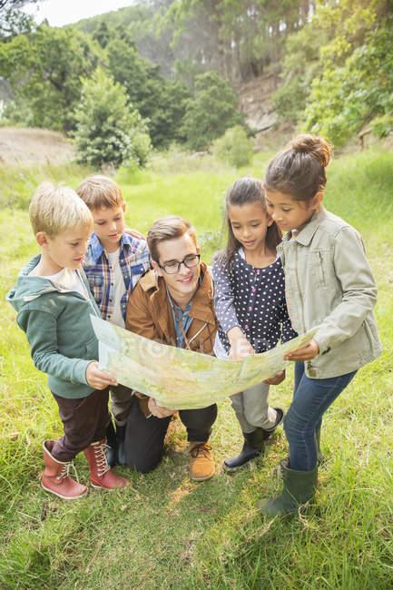 Ученики и преподаватели читают карту в поле — стоковое фото