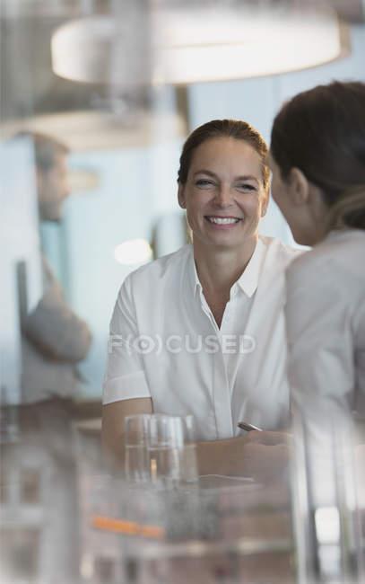 Улыбаться говорить в совещание женщин-предпринимателей — стоковое фото