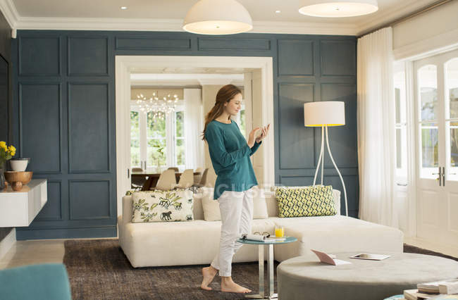 Woman texting with cell phone in home showcase living room — Stock Photo