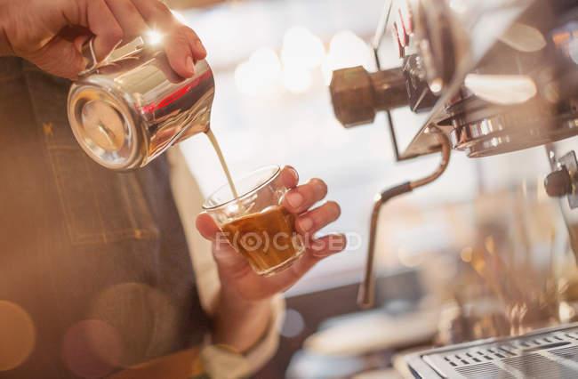 Barista gießt Milch in Espresso an der Espresso-Maschine im Café hautnah — Stockfoto