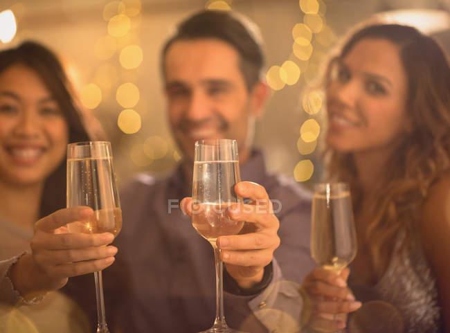 Друзья-портретисты пьют шампанское за флейты — стоковое фото