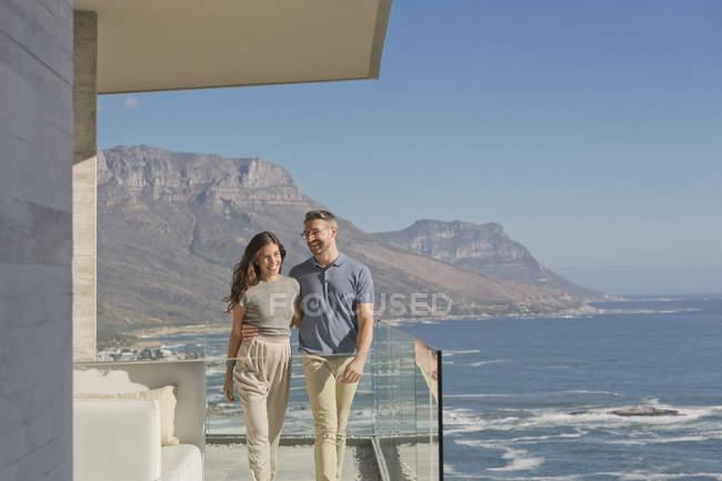 Coppia sorridente che cammina su un balcone di lusso con vista soleggiata sull'oceano e sulle montagne — Foto stock
