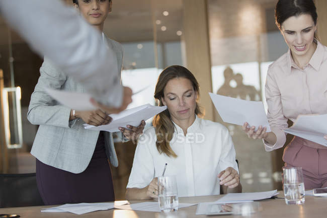 Business people signing and reviewing paperwork in conference room meeting — Stock Photo