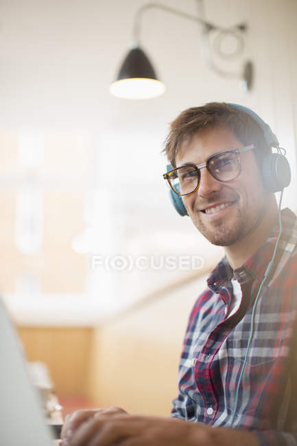 Glücklicher junger Mann mit Kopfhörern und Laptop — Stockfoto