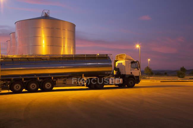 Tanque de aço inoxidável leite estacionado ao lado da torre de armazenamento de silagem, à noite — Fotografia de Stock