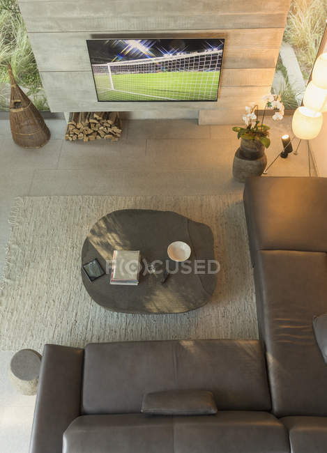 View from above soccer game on TV in modern, luxury home showcase interior living room — Stock Photo
