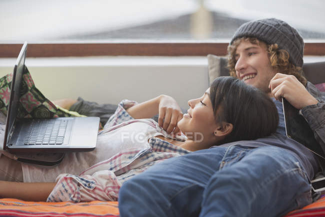 Young couple relaxing laying using laptop — Stock Photo