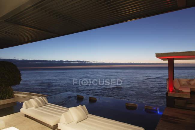 Диваны и бесконечный бассейн с видом на океан — стоковое фото