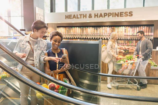 Giovane coppia lesbica utilizzando il telefono cellulare sulla scala mobile nel mercato dei negozi di alimentari — Foto stock