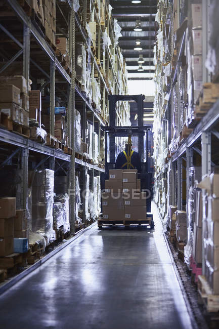 Worker driving forklift with cardboard boxes in aisle of distribution warehouse — Stock Photo