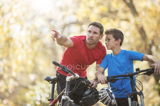 Père pointant et expliquant au fils sur les vélos de montagne — Photo de stock