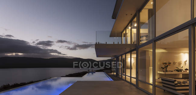 Tranquil modern luxury home showcase exterior with illuminated infinity pool and dusk ocean view — Stock Photo