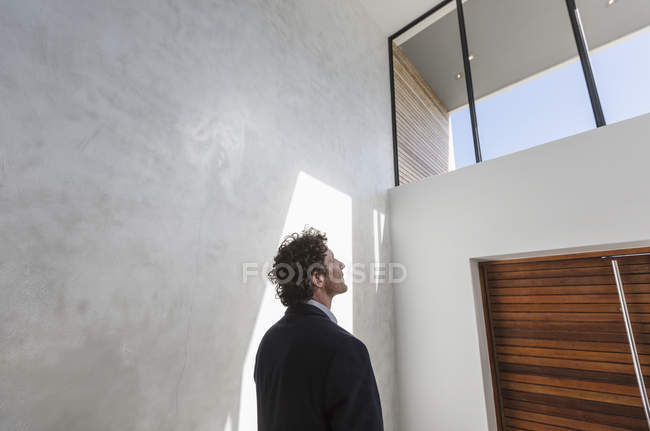 Pensive businessman looking up at window — Stock Photo