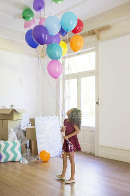 Chica joven sosteniendo globos en el espacio de vida - foto de stock