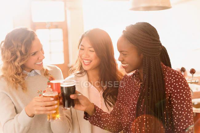 Amigos de mulheres brindando copos de cerveja em bar — Fotografia de Stock