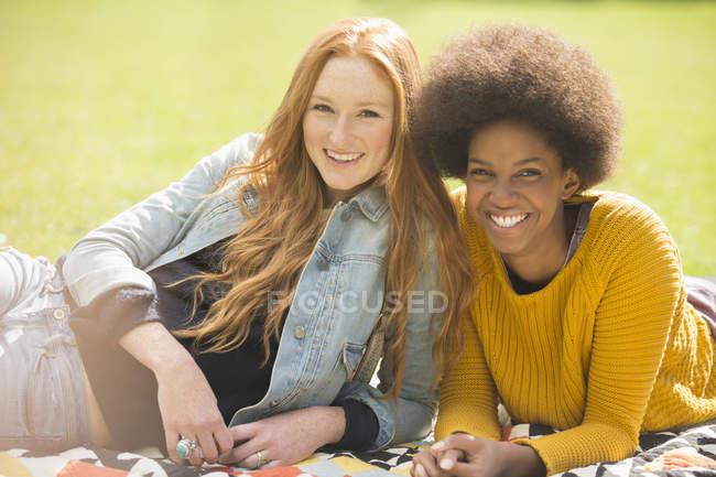 Felici giovani donne che si rilassano insieme nel parco — Foto stock