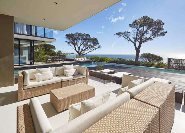 Moderne Luxus nach Hause Schaufenster Patio mit sonnigen Meerblick — Stockfoto
