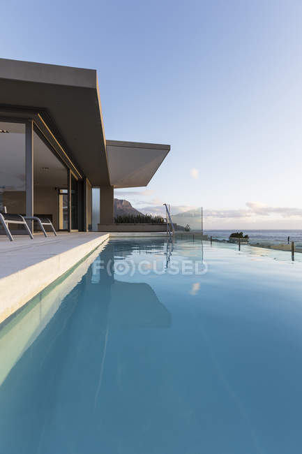 Tranquil blue lap swimming pool outside modern luxury home showcase exterior — Stock Photo