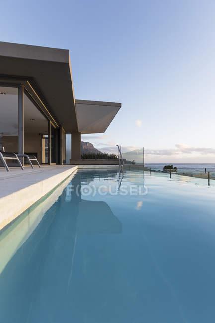 Спокойный синий бассейн у витрины современного роскошного дома. — стоковое фото