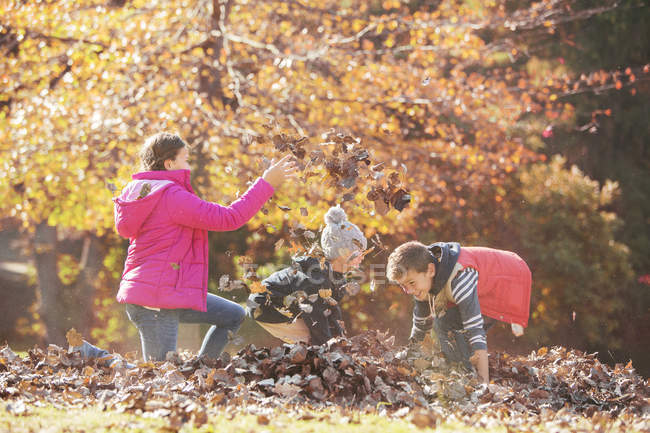 Boys and girl playing in autumn leaves — Stock Photo