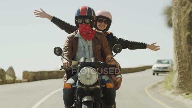 Mulher jovem exuberante andando de moto na estrada ensolarada — Fotografia de Stock