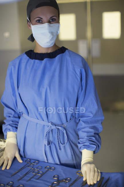 Portrait de chirurgien masqué avec set d'instruments chirurgicaux dans le théâtre d'opération — Photo de stock