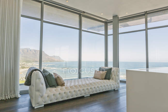 Tufted chaise lounge at luxury home showcase interior window with ocean view — Stock Photo