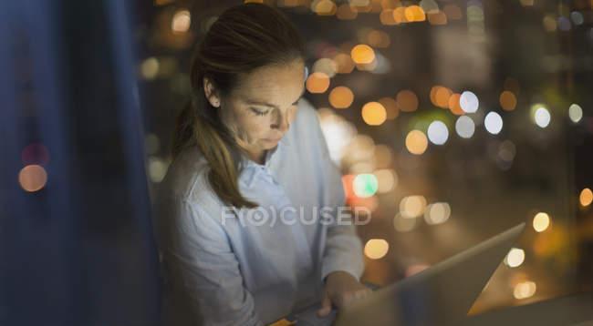 Donna d'affari seria e concentrata che lavora fino a tardi al computer portatile nella finestra dell'ufficio di notte — Foto stock