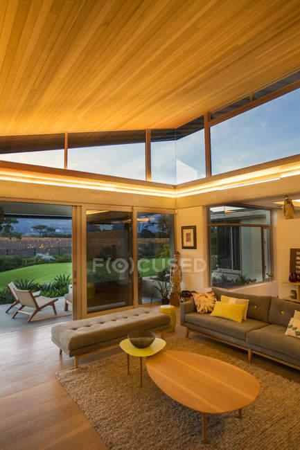 Освещённый деревянный потолок над роскошной гостиной с видом на внутренний дворик — стоковое фото
