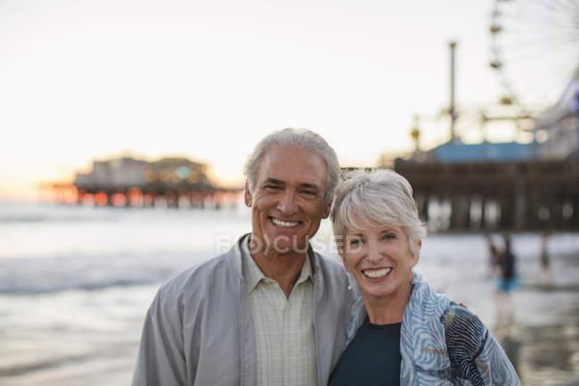 Porträt eines lächelnden Seniorehepaares am Strand — Stockfoto