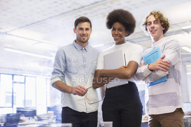 Happy young business people smiling in office — Stock Photo