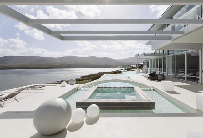 Сонячна, спокійна сучасну розкіш додому Вітрина екстер'єр із плавальним басейном та видом на океан — стокове фото
