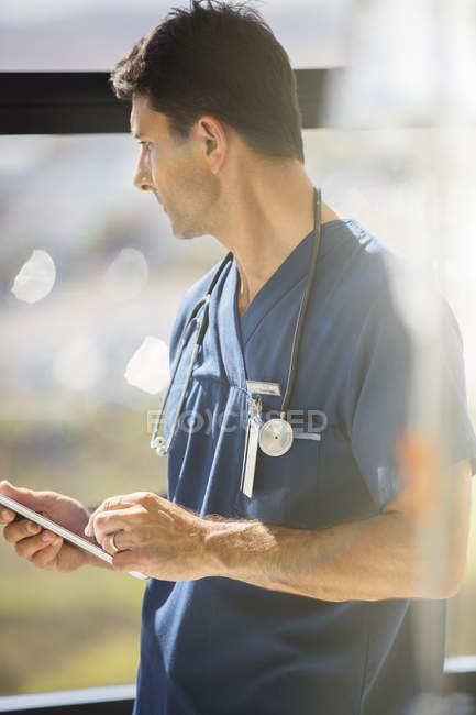 Male doctor holding tablet pc and looking out of hospital window — Stockfoto