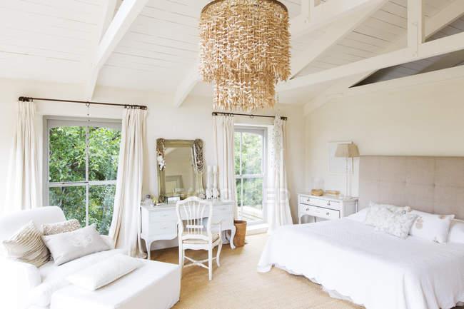 Люстра и кресло в сельский спальни — стоковое фото