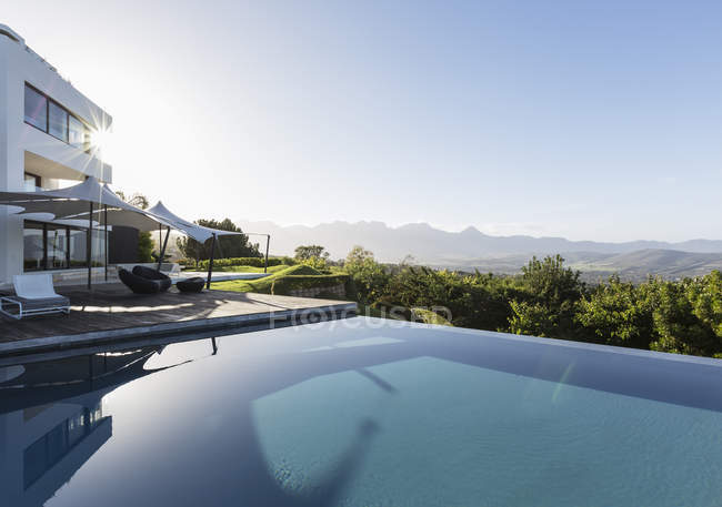 Tranquil, sunny home showcase exterior with infinity pool and mountain view under blue sky — Stock Photo