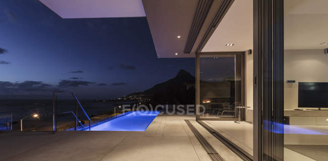 Illuminated blue lap swimming pool outside modern luxury home showcase exterior at night — Stock Photo