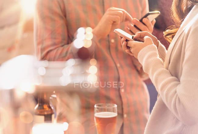 Mann und Frau schreiben SMS mit Handy und trinken Bier an Bar — Stockfoto