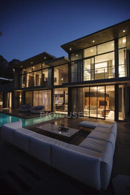 Divano sezionale a bordo piscina della casa di lusso di notte — Foto stock