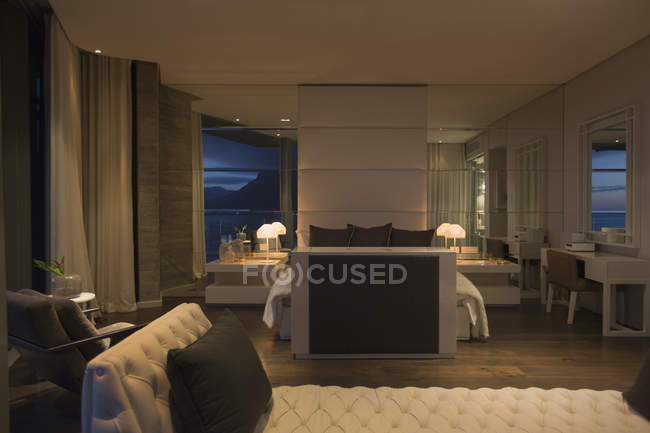 Иллюминированная спальня роскошного дома с витриной ночью — стоковое фото