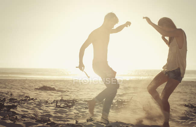 Playful couple dancing on sunny beach at sunset — Stock Photo