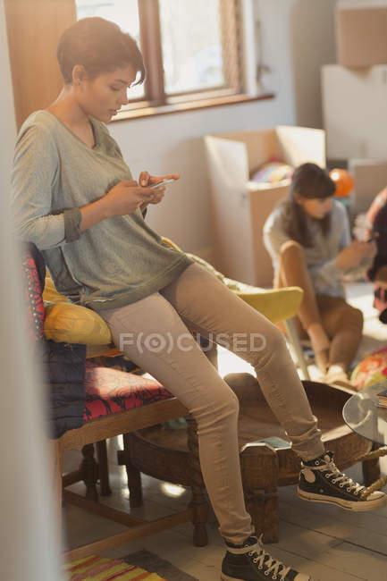 Mujer joven mensajes de texto con teléfono celular en nuevo apartamento - foto de stock