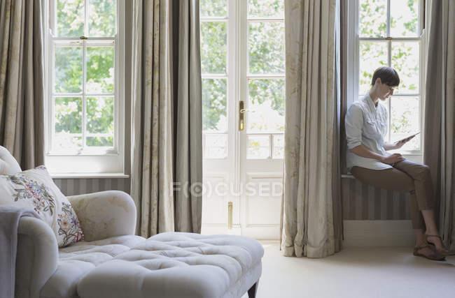 Жінка сидить на вікна і використовуючи цифровий планшетний — стокове фото