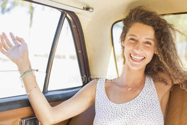 Mulher sentindo brisa da janela do carro do banco de trás — Fotografia de Stock