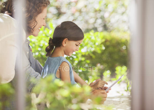 Granddaughter playing on digital tablet with granddaughter — Stock Photo