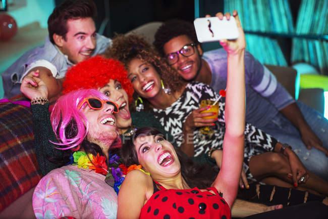 Gruppe von Freunden nehmen Selfie auf Sofa auf party — Stockfoto