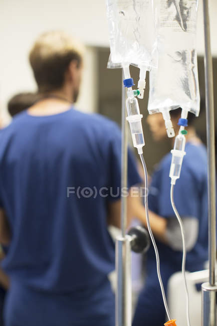 Close up of drip bags, doctors in background — стоковое фото