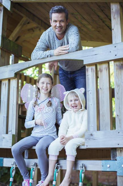 Pai e crianças brincando no playset — Fotografia de Stock